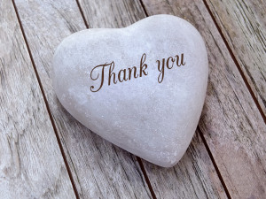 """""""Thank You"""" engraved on a heart shaped pebble lying on a wooden boardwalk - Dating & Singles Events Testimonials"""